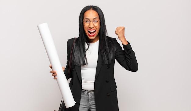 Молодая чернокожая женщина агрессивно кричит с сердитым выражением лица или со сжатыми кулаками, празднуя успех. концепция архитектора