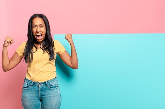 Молодая чернокожая женщина агрессивно кричит с сердитым выражением лица или со сжатыми кулаками, празднуя успех. копировать космическую концепцию