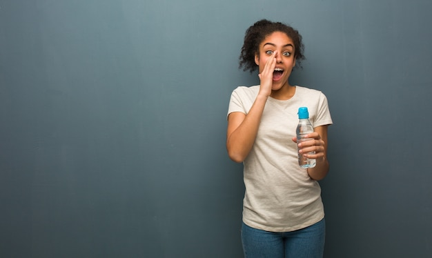 Young black woman shouting something happy to the front. she is holding a water bottle.
