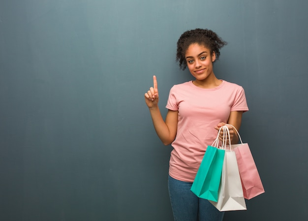 Young black woman showing number one. she is holding a shopping bags.