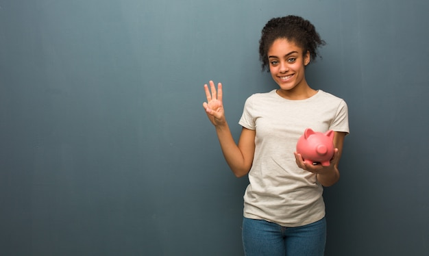 Young black woman showing number three. she is holding a piggy bank.