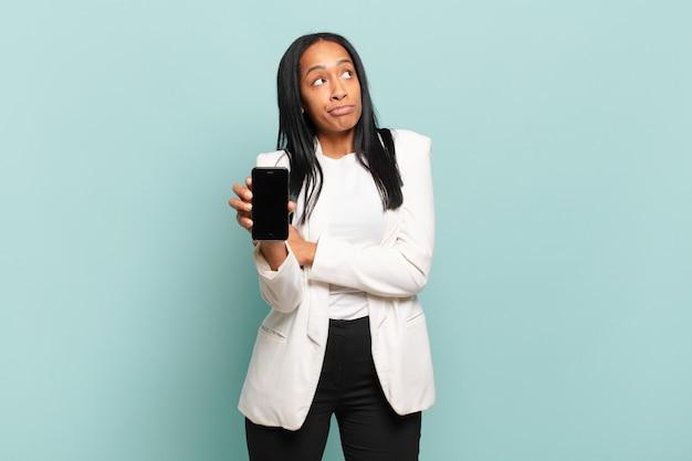 젊은 흑인 여성이 어깨를 으쓱하고 혼란스럽고 불확실하다고 느끼며 팔짱을 끼고 어리둥절한 표정으로 의심합니다. 스마트 폰 개념