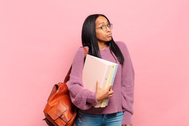 Молодая чернокожая женщина пожала плечами, чувствуя смущение и неуверенность, сомневаясь, скрестив руки и озадаченный взгляд. студенческая концепция