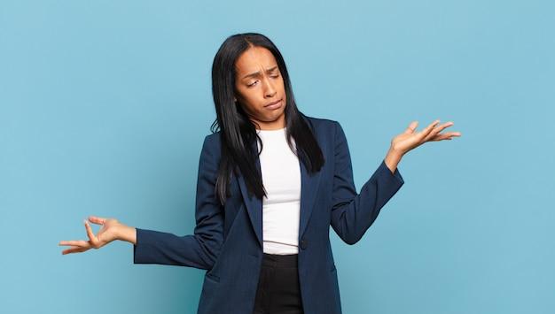 멍청하고, 미쳤고, 혼란스럽고, 어리둥절한 표정으로 어깨를 으쓱하는 젊은 흑인 여성, 짜증나고 무의미한 느낌. 비즈니스 개념
