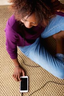 携帯電話で床に座っている若い黒人の女性