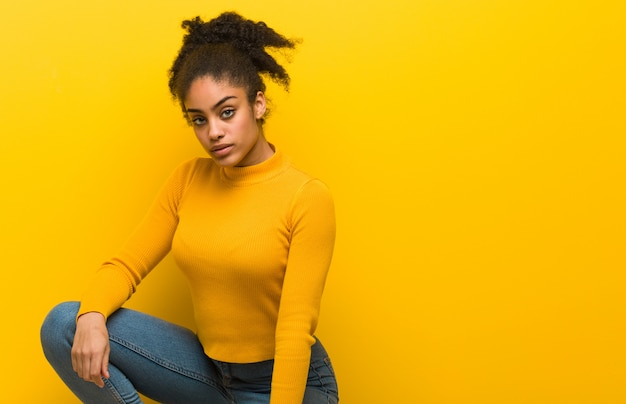 Young black woman sitting over an orange wall