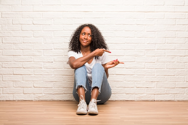 Young black woman sitting on a wooden floor confused and doubtful man, decide between two options, concept of indecision