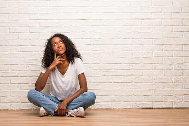 Young black woman sitting on a wooden floor doubting and confused, thinking of an idea or worried about something