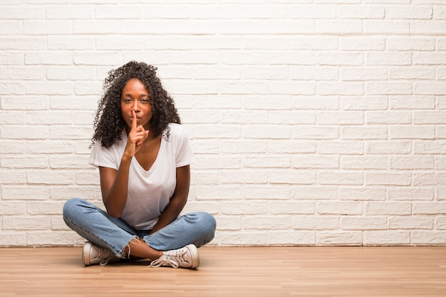 Young black woman sitting on wooden floor keeping a secret or asking for silence
