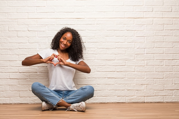 Young black woman sitting on a wooden floor making a heart with hands, expressing the concept of love and friendship, happy and smiling