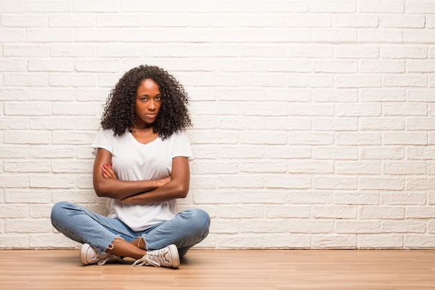 Young black woman sitting on wooden floor very angry and upset, very tense