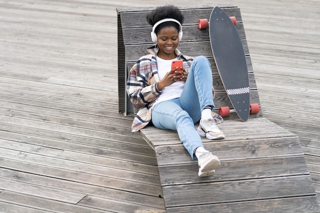 Young black woman skater hold smartphone text sit on bench in urban space with longboard messaging