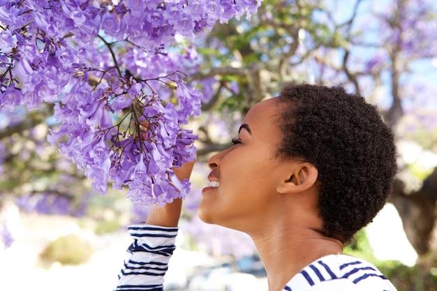 樹木に花を咲かせる若い黒人女性