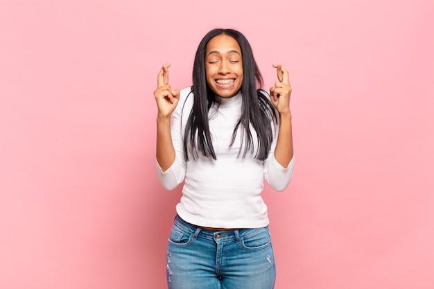 笑顔で心配そうに両指を交差させ、心配を感じ、幸運を願ったり期待したりする若い黒人女性