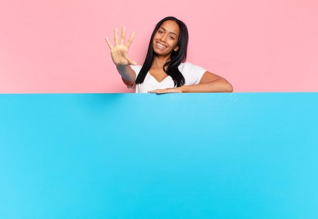젊은 흑인 여자 웃 고 친절 하 게 찾고, 앞으로 손으로 번호 5 또는 5를 보여주는 카운트 다운. 복사 공간 개념