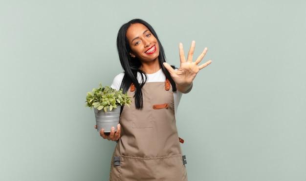 Молодая темнокожая женщина улыбается и выглядит дружелюбно, показывая пятый или пятый номер рукой вперед