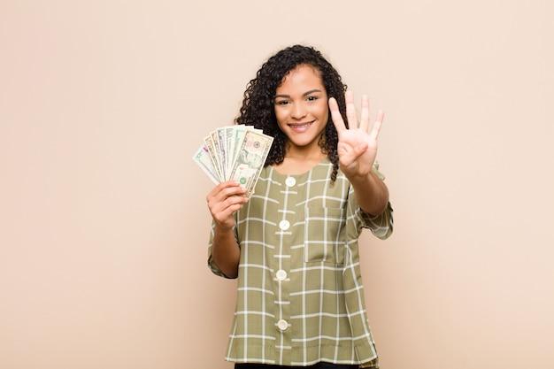 Молодая темнокожая женщина улыбается и выглядит дружелюбно, показывает номер четыре или четвертый с рукой вперед, считая, держа долларовые банкноты