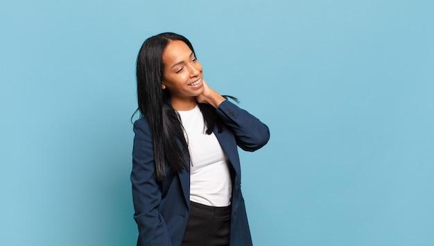 Молодая чернокожая женщина весело и небрежно улыбается, взявшись за голову с позитивным, счастливым и уверенным взглядом. бизнес-концепция