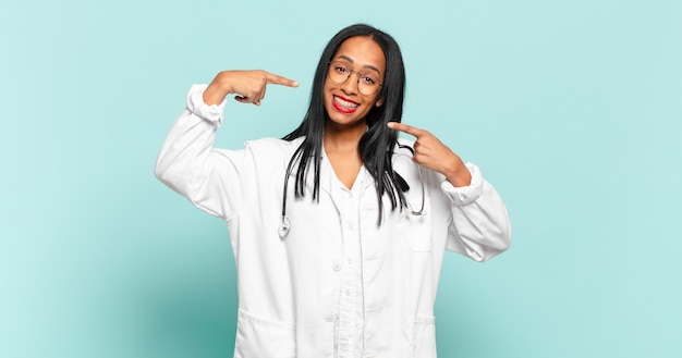 Young black woman smiling confidently pointing to own broad smile, positive, relaxed, satisfied attitude. physician concept