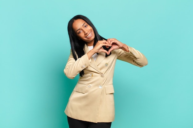 Young black woman smiling and feeling happy, cute, romantic and in love, making heart shape with both hands. business concept