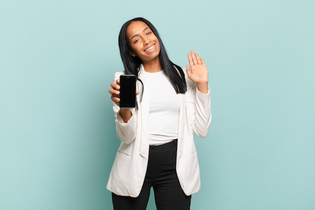 Молодая темнокожая женщина счастливо и весело улыбается, машет рукой, приветствует и приветствует вас или прощается. концепция смартфона