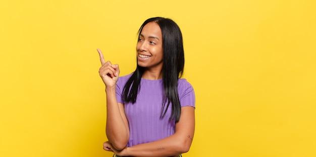 젊은 흑인 여성이 행복하게 웃고 옆으로보고 궁금해하고 생각하거나 아이디어가 있습니다.