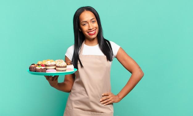 Молодая темнокожая женщина счастливо улыбается, положив руку на бедро и уверенно, позитивно, гордо и дружелюбно. концепция шеф-повара пекарни