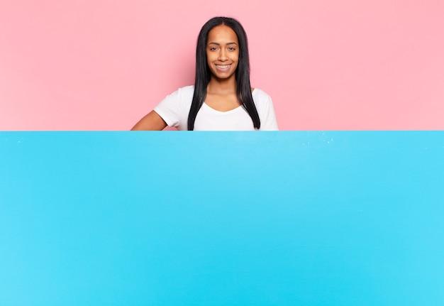 엉덩이와 자신감, 긍정적이고 자랑스럽고 친절한 태도에 손으로 행복하게 웃는 젊은 흑인 여성. 복사 공간 개념