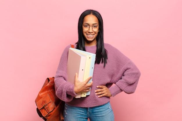 腰に手を当てて幸せそうに笑っている若い黒人女性と自信を持って、前向きで、誇りに思って、フレンドリーな態度。学生の概念