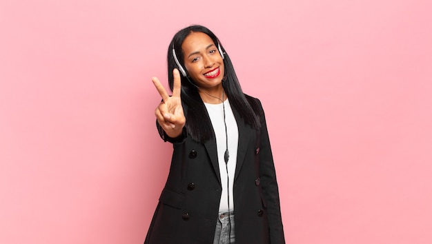 Young black woman smiling and looking friendly, showing number two or second with hand forward, counting down. telemarketing concept