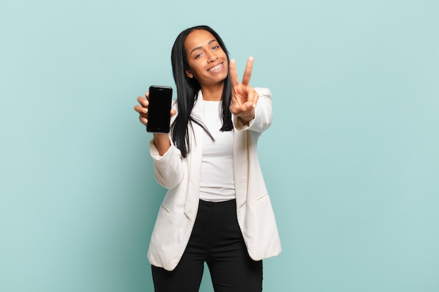 Young black woman smiling and looking happy, carefree and positive, gesturing victory or peace with one hand. smart phone concept