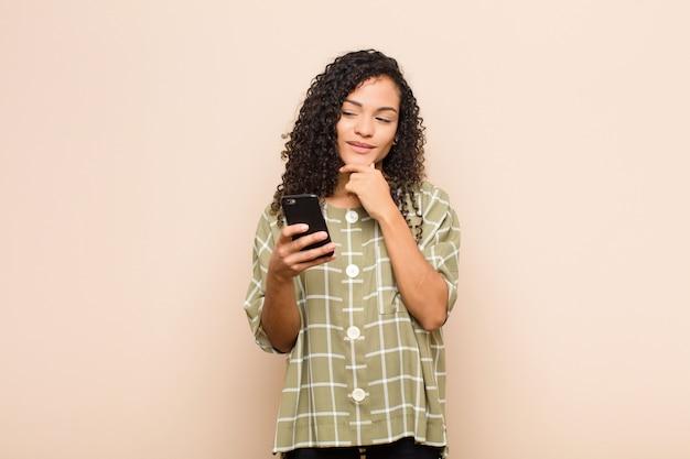 턱에 손으로 행복하고 자신감있는 표정으로 웃고 궁금해하고 스마트 폰으로 옆을 바라 보는 젊은 흑인 여성