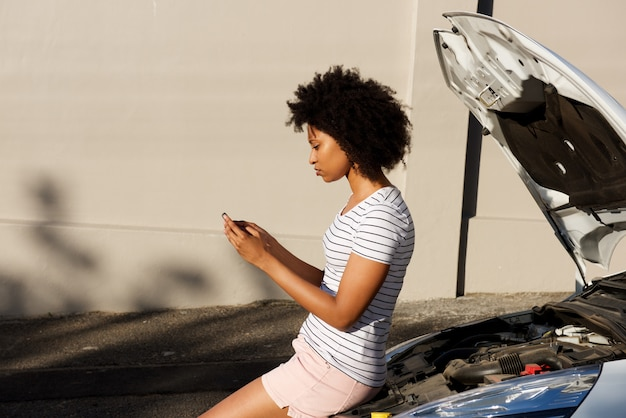 若い黒人女性が壊れた車で立って、支援のために携帯電話を使用