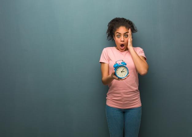 Молодая чернокожая женщина удивлена и шокирована. она держит будильник.