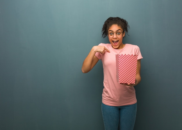 若い黒人女性は驚いて、成功と繁栄を感じています。彼女はポップコーンのバケツを持っています。