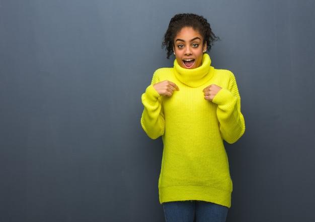 若い黒人女性は驚き、成功と繁栄を感じます