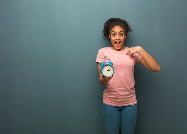 Young black woman surprised, feels successful and prosperous. she is holding an alarm clock.