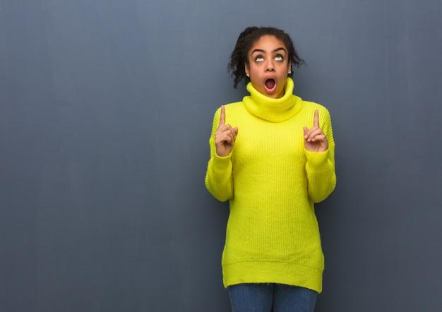 若い黒人女性が何かを表示する上向きに驚いた