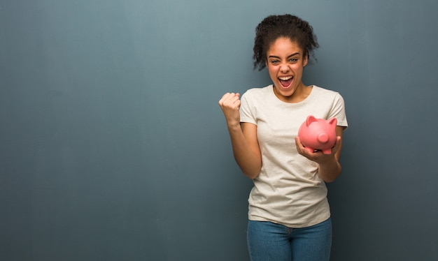Young black woman surprised and shocked. she is holding a piggy bank.