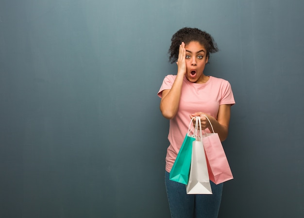 Young black woman surprised and shocked she is holding a shopping bags