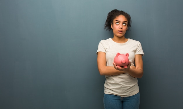 Young black woman tired and bored. she is holding a piggy bank.