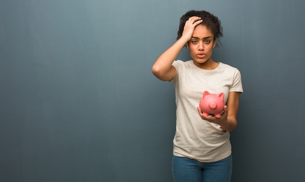Young black woman tired and very sleepy. she is holding a piggy bank.