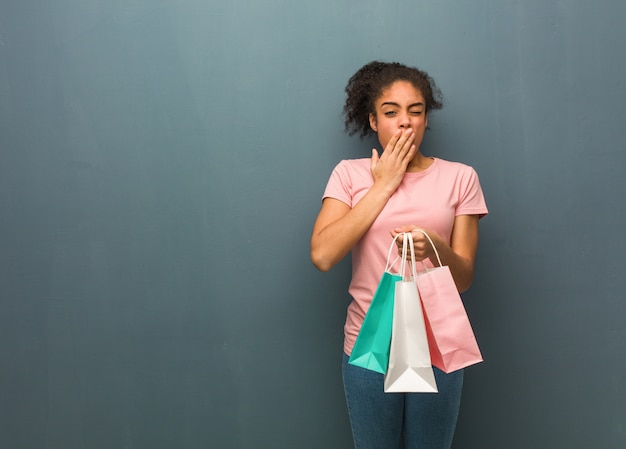 Young black woman tired and very sleepy. she is holding a shopping bags.