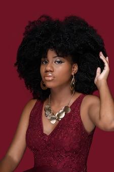 若い黒人女性は、赤い背景で隔離の赤いドレスとアフロベンケア髪で彼女の手に触れます