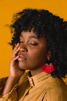 Young black woman touching face with closed eyes