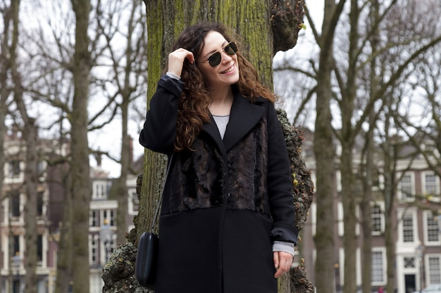 Young black woman touching tree park nature girl winter portrait smile spring coat long hair curly mood shore sity
