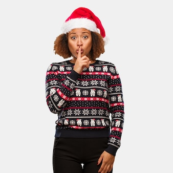 Young black woman in a trendy christmas sweater with print keeping a secret or asking for silence
