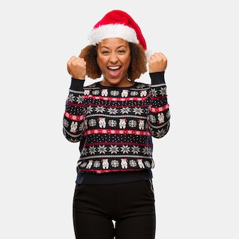 Young black woman in a trendy christmas sweater with print surprised and shocked