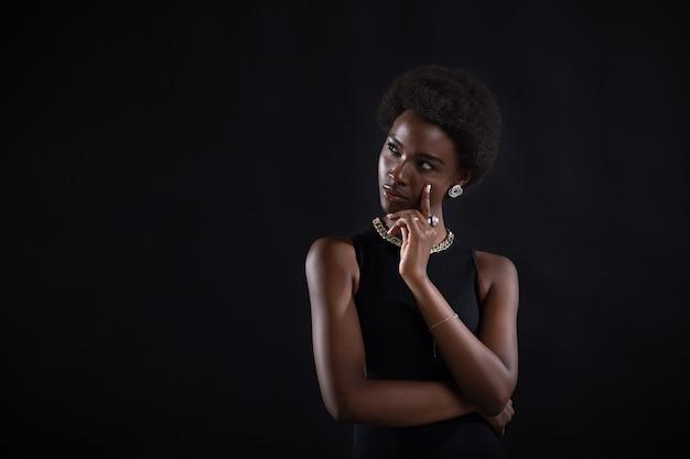 Молодая темнокожая женщина пытается найти лучшее решение и ищет ответ. афро-американская женщина с сомнительным выражением лица смотрит в сторону и держит рукой за подбородок на черном фоне