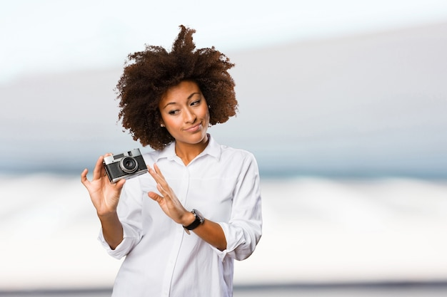 빈티지 카메라를 사용하는 젊은 흑인 여성